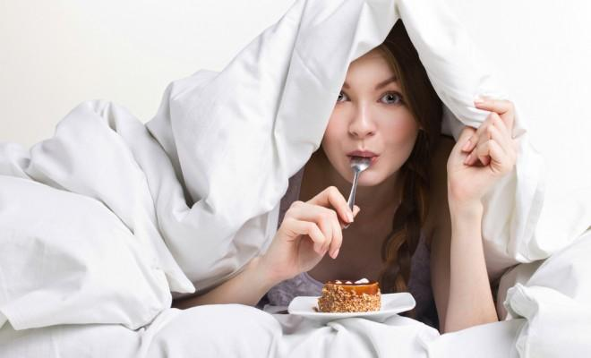 Woman eats food in bed