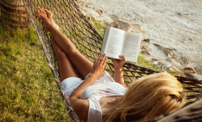 Woman reads book in hammock on beach