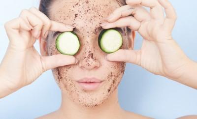 Woman with exfoliator on her skin holding cucumbers in front of her eyes
