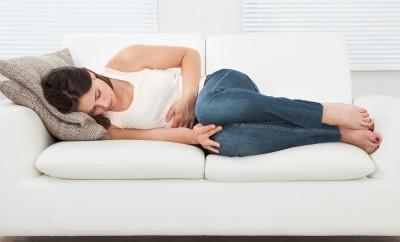 Woman laying on couch suffering from symptoms of PMS
