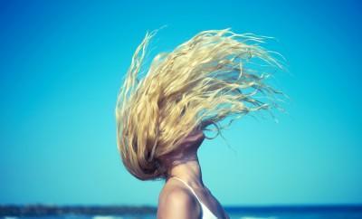Girl on beach flips her hair