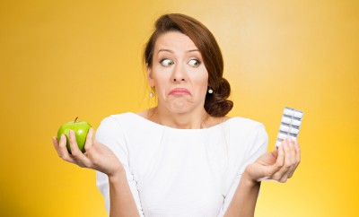 Woman shrugging her shoulders while holding an apple and a pill container