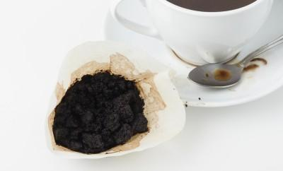 Used coffee grounds beside a cup of coffee